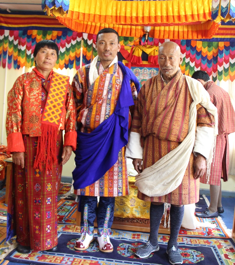 Australia Awards alumnus Ugyen Namgay with his proud parents at the conferral of the Blue Scarf and honorary sword by HisMajesty the King